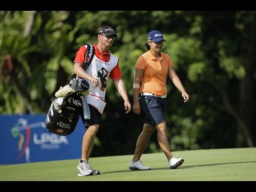La nº 1 del mundo, Yani Tseng, camina junto a su 'caddie', Jason Hamilton, durante la tercera ronda del torneo de Singapur