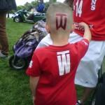 Un niño con la camiseta y logo deTiger Woods pintado en la cabeza