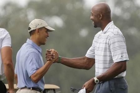 Barak Obama y Alonzo Mourning estrechan su mano. Foto: AP