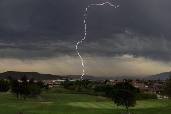Imagen de un campo de golf y de la caída de un rayo durante una tormenta
