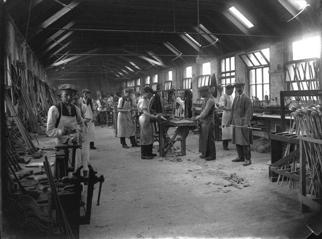 Imagen de un fabricante de palos británico alrededor de 1915. EL aspecto era similar a una gran carpintería, donde se ven aprendices y oficiales, y en primer término a la derecha el Clubmaker.